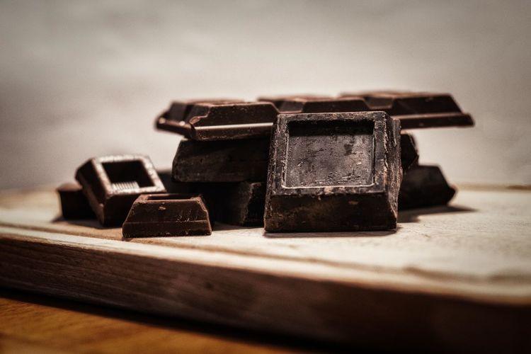 Dark chocolate peaces on wood