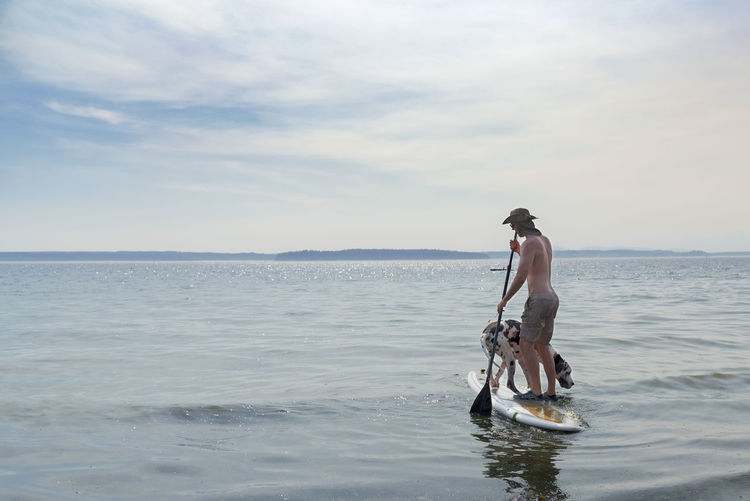 Shirtless man paddleboarding with dog in sea against sky
