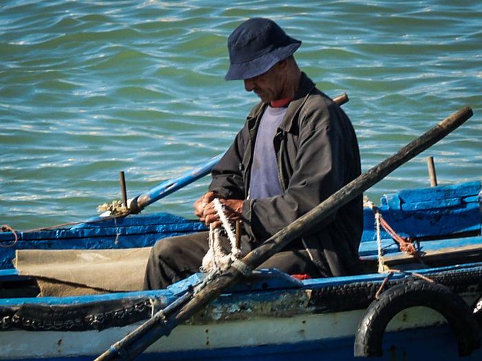 Man fishing in boat sailing in sea