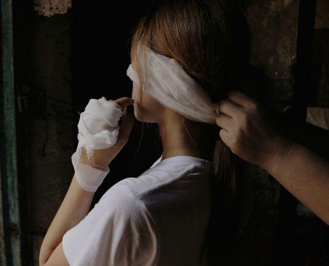 Cropped hand tying bandage on face