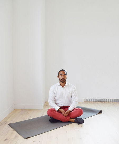 Young Man Meditating On Yoga Mat Against White Wall In Room