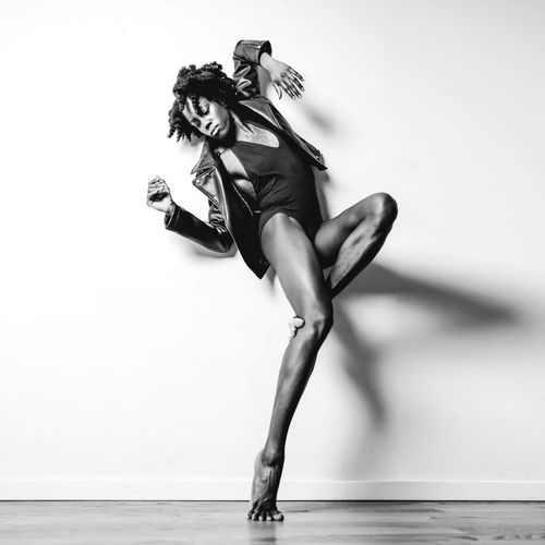 Portrait of woman dancing against white background
