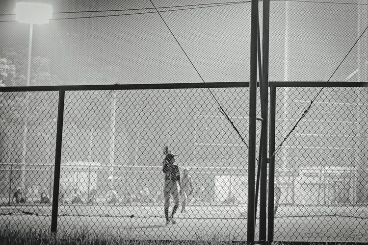 Rear view of man standing by chainlink fence