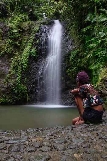 Woman sitting on rock looking at waterfall