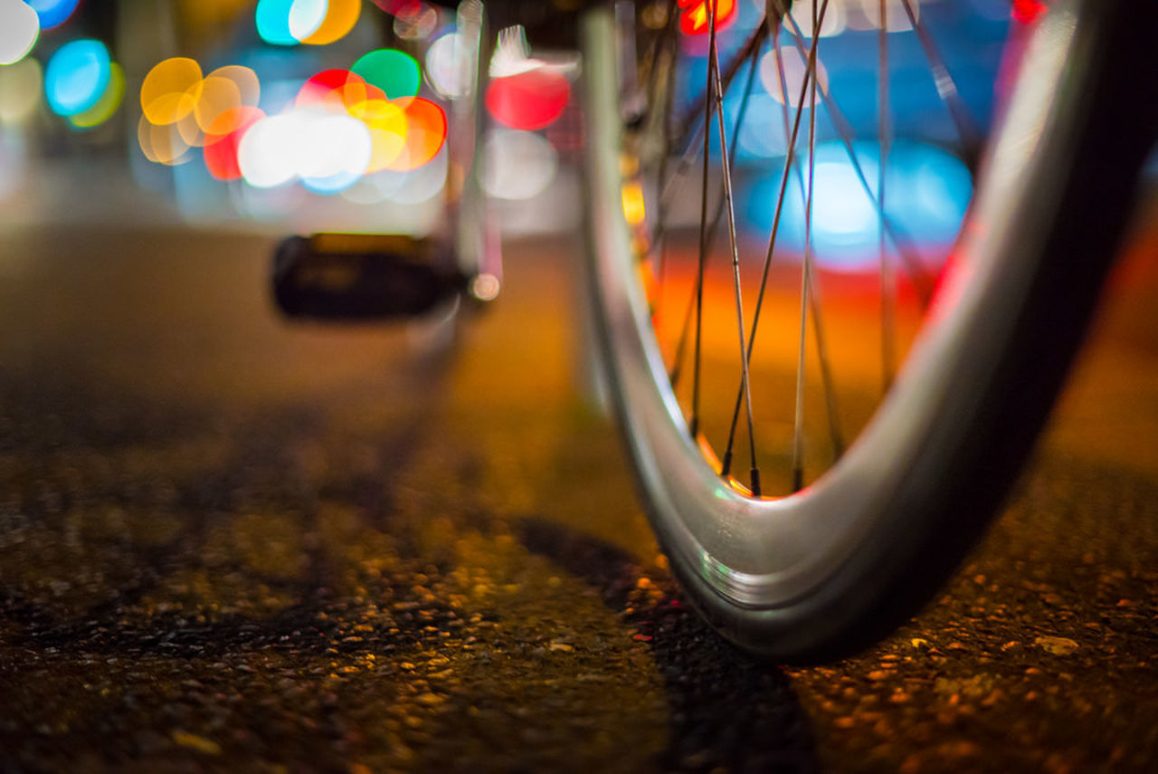 transportation, night, selective focus, no people, land vehicle, close-up, bicycle, illuminated, road, mode of transport, outdoors, wheel, multi colored