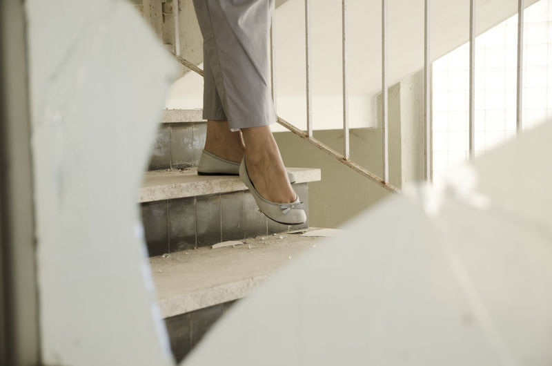 Low Section Of Woman Walking On Steps At Home