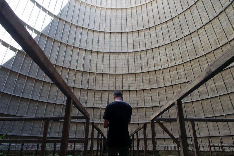 Man Standing Amidst Railings Against Buildings