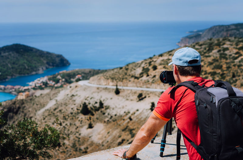 Rear View Of Backpacker Photographing On Mountain Against Sky During Sunny Day