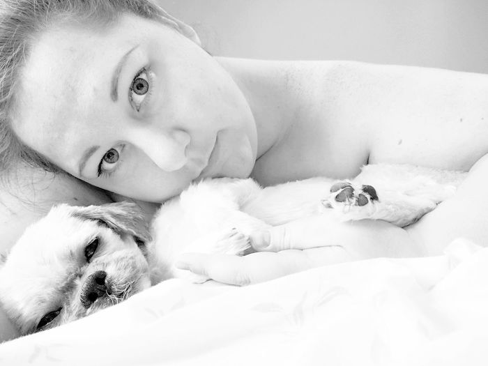 Portrait Of Young Woman With Dog Lying Down On Bed At Home