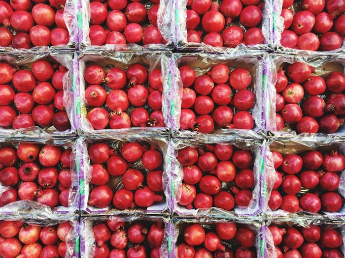Full frame shot of pomegranates in containers at market for sale