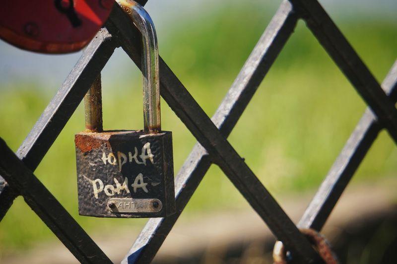 Close-up of love padlocks hanging on metal chain