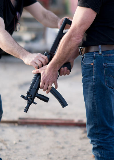 Midsection Of Men Holding Gun