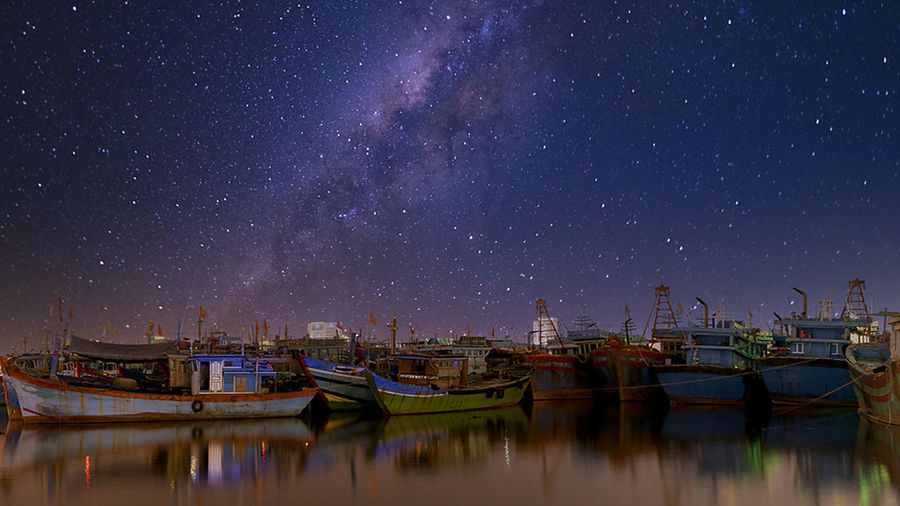 Boats moored in lake against sky at night