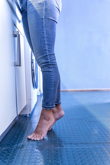Feet of a woman standing on tiptoe at home in the kitchen One Person Low Section Jeans barefoot Human Leg Body Part Human Body Part Real People Lifestyles Indoors  Standing Casual Clothing Women Flooring Adult Blue Leisure Activity Human Foot Tiled Floor Human Limb Kitchen Tiptoe Woman Females Jeans Indoors  Inside Home Interior Cleaning Washing Countertop Young Adult Beautiful Housemaid Housewife Domestic