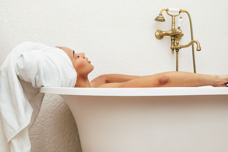 Woman Domestic Bathroom Bathtub Bathroom Home Taking A Bath Hygiene Indoors  Relaxation Lifestyles One Person Lying Down Washing Luxury Eyes Closed  Side View Hygiene Towel Relaxing Wellbeing Body Care Skin Care