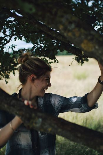 Smiling young woman holding tree branches