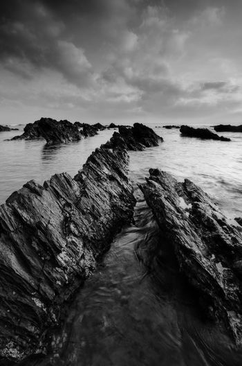 Amazing rock formations at Pandak beach, Terengganu in black and white monochrome fine art technique.  Nature composition blur soft focus noise visible due to long exposure effect. Black And White Fishing Boat Landscape Fine Art Boat Amazing View Black&white Fine Art Photography Black Amazing Malaysia EyeEm Nature Lover EyeEm Wallpaper Sunset Sunrise Backgrounds Kelantan Blackandwhite Art Water Sea Beach Wave Sand Rock - Object Sky Horizon Over Water Cloud - Sky Tide Low Tide Seascape