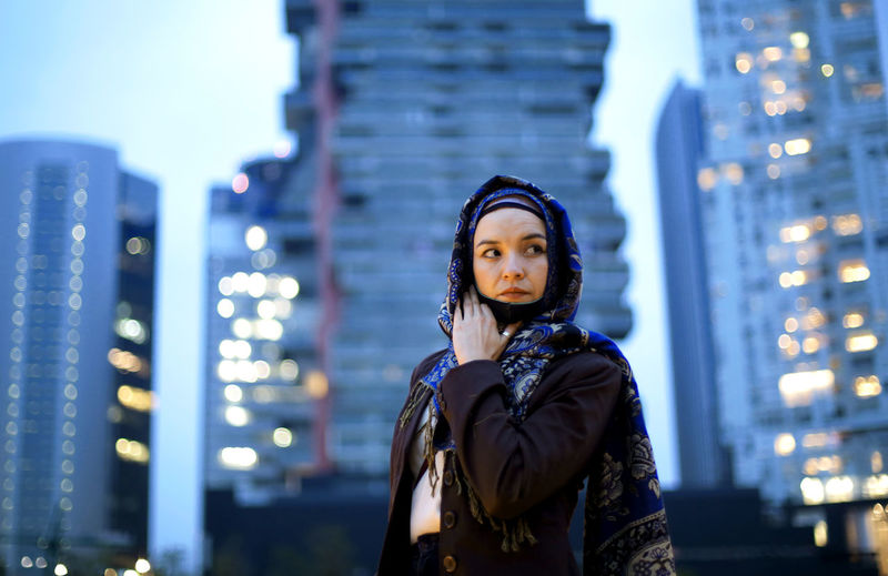 Portrait of young woman standing against illuminated city at night