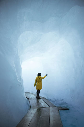 Rear view of woman standing in snow cave