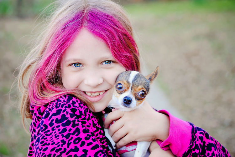 PORTRAIT OF A GIRL With Pink Hair Holding Puppy