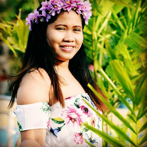 Portrait of smiling young woman wearing floral wreath standing by plants