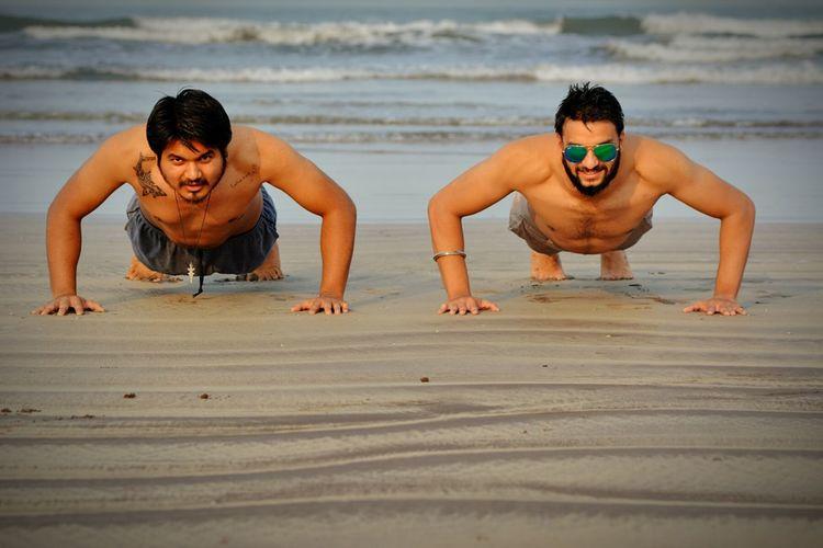 Young Men Doing Push Ups On Beach