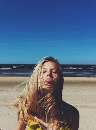 Young woman with eyes closed sticking out tongue while standing at beach against blue sky