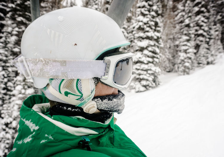 A woman in a ski helmet rides up a lift with snowy pine trees in the background Adventure Close-up Cold Temperature Crash Helmet Cycling Helmet Day Hardhat  Headshot Headwear Helmet Nature One Person Outdoors People Protection Ski Goggles Snow Snowboarding Snowing Sport Sports Helmet Warm Clothing Winter Work Helmet