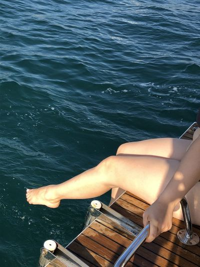 Low section of woman on boat in sea