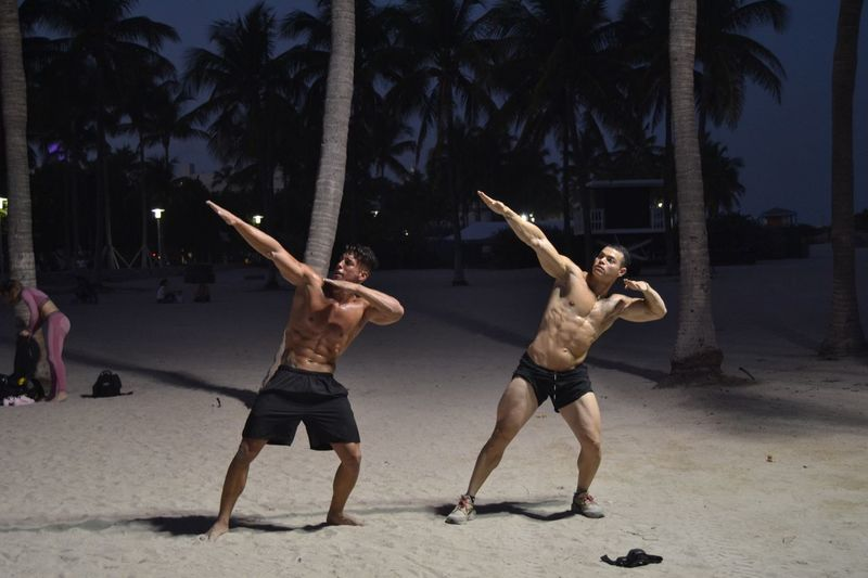 Full length of shirtless muscular men gesturing while standing at beach during night