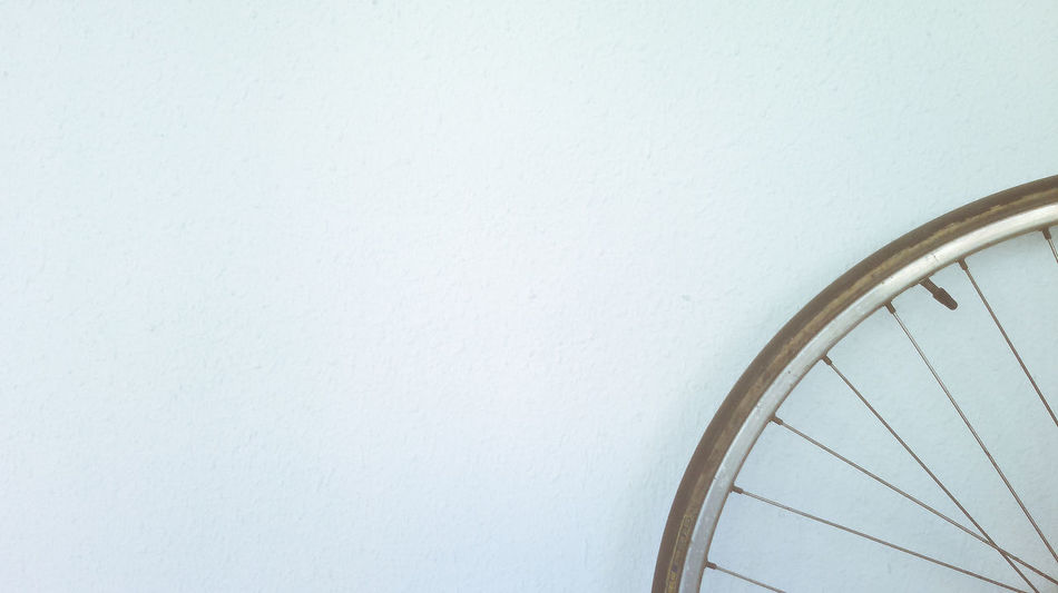 Bike wheel over white wall Cyclo Horizontal Less Is More Wheel Bicycle Bike Close-up Color Image Copy Space Indoors  No People Quarter  Simplicity White Background