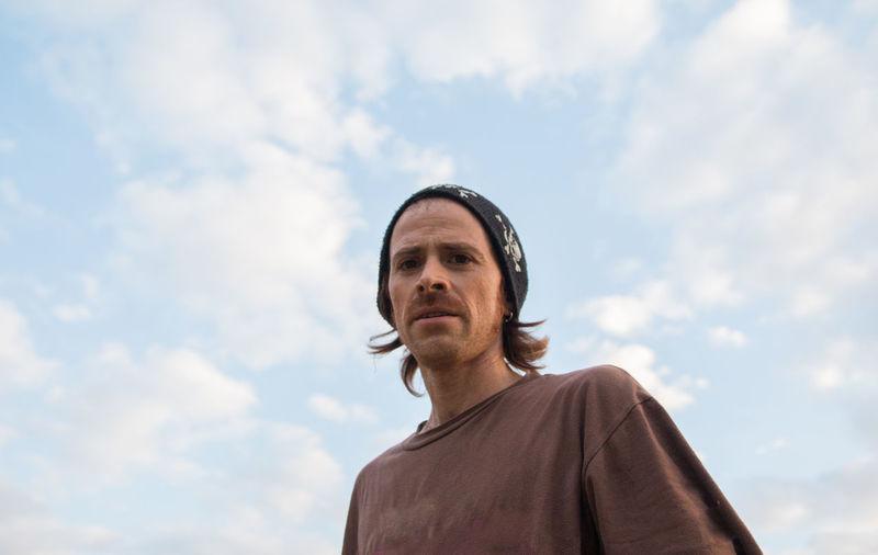 Portrait of trendy man against cloudy sky