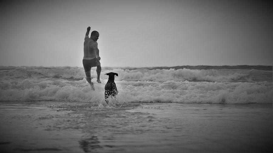 Man running with dog at beach