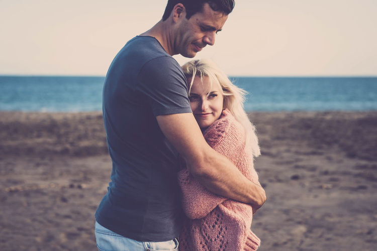 Couple embracing on beach against sky