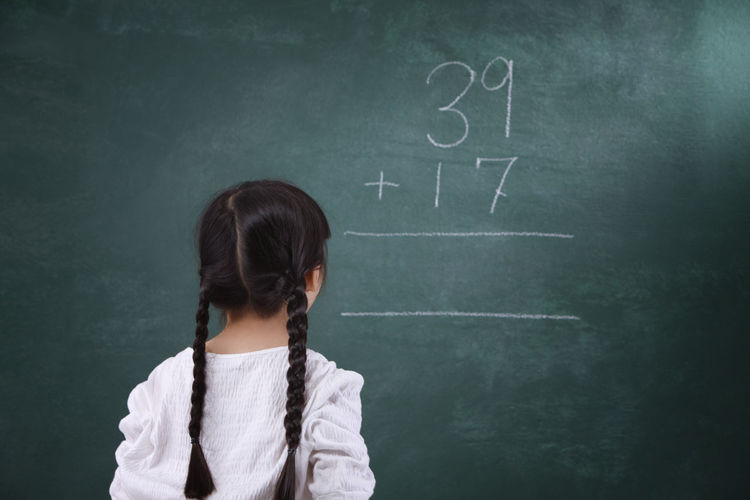 Rear view of girl learning mathematics on blackboard