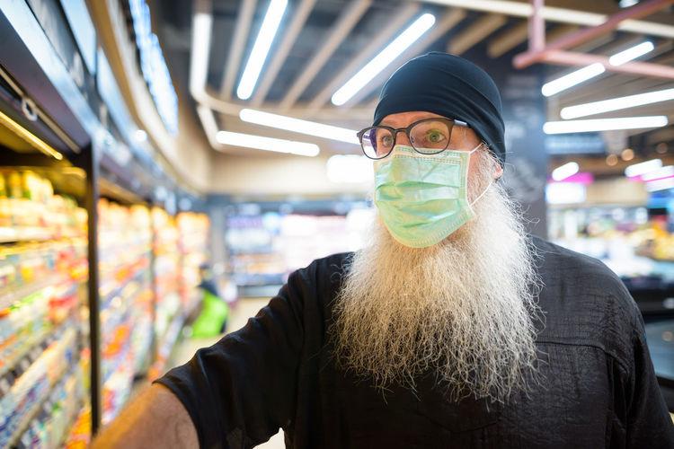 Mature man wearing mask in shopping mall