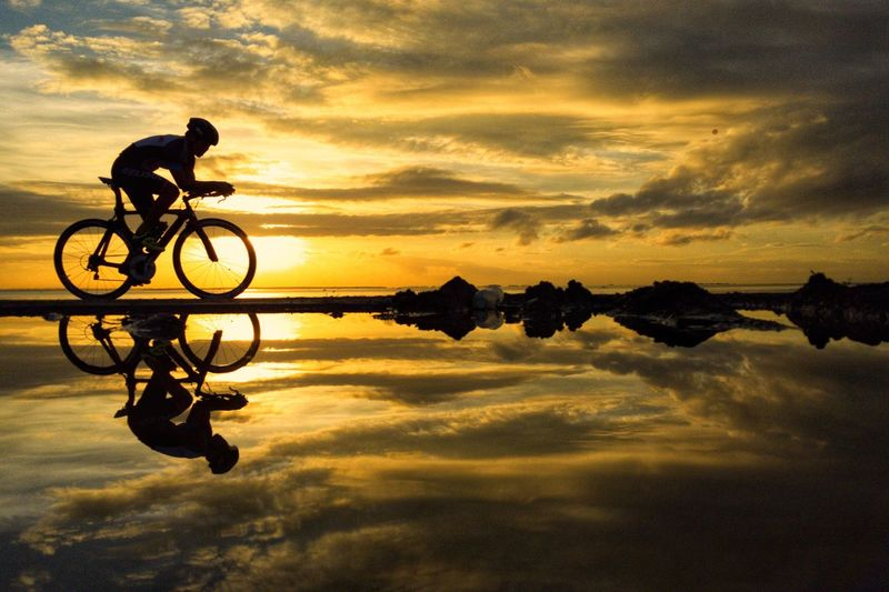 Silhouette man cycling on bicycle against sky during sunset