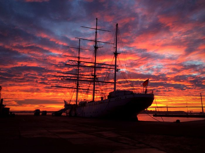 Silhouette sailboats moored on sea against dramatic sky during sunset