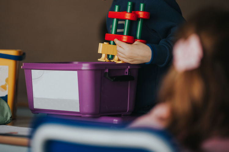 Midsection of boy holding toy in classroom