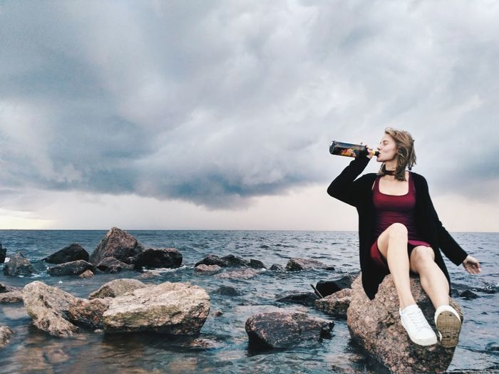 Carefree young woman drinking alcohol while sitting on rock against sea and cloudy sky