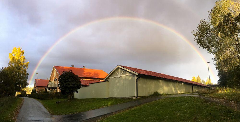 Rainbow over building and houses against sky