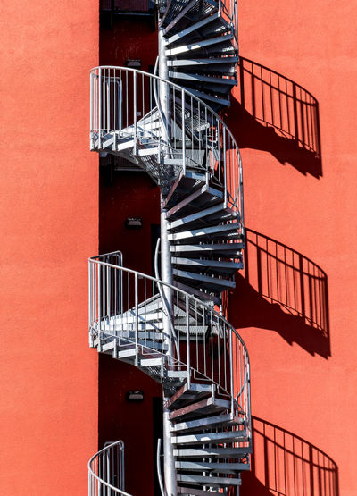 Spiral staircase on orange building wall during sunny day