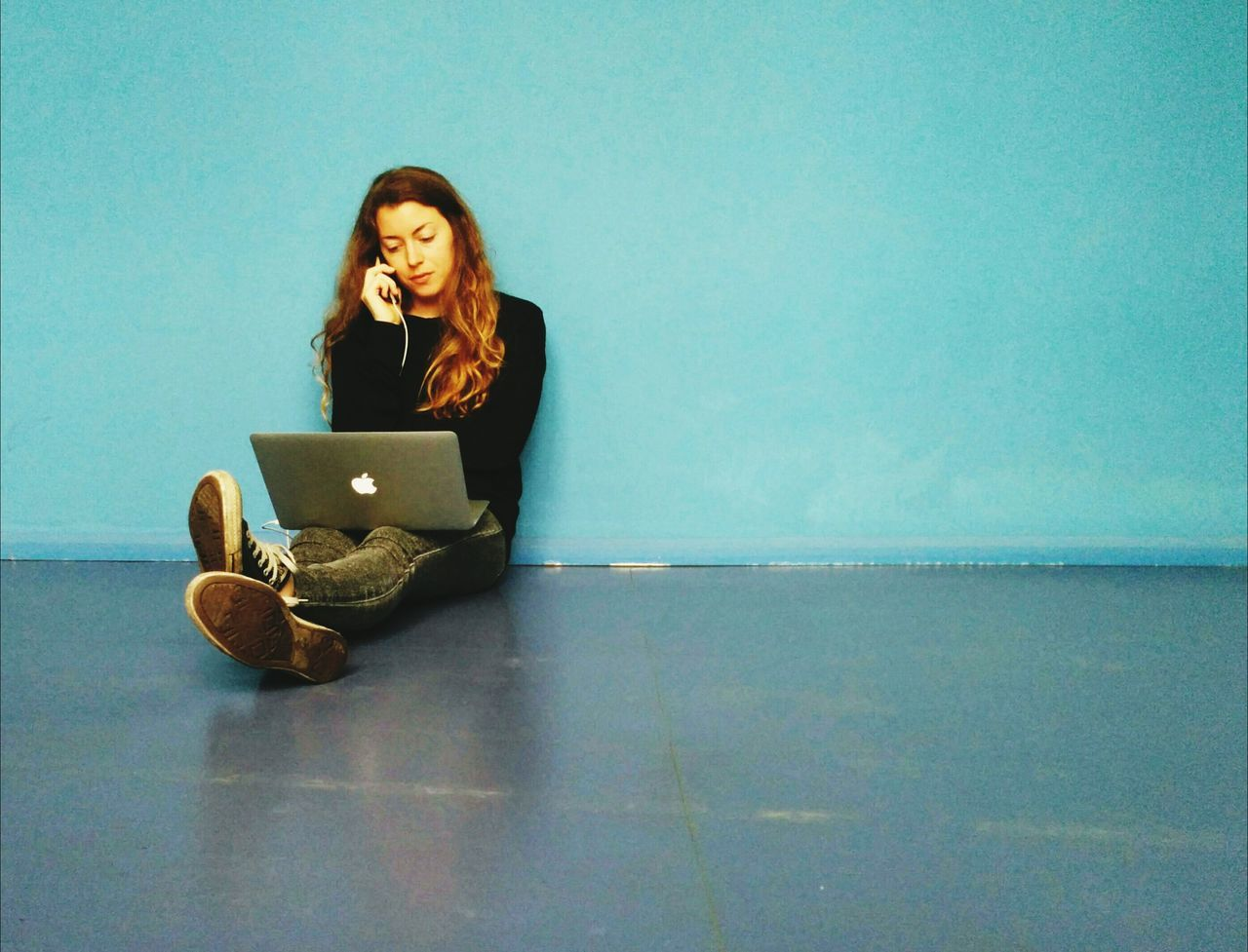 Young woman talking on phone while sitting on floor with laptop