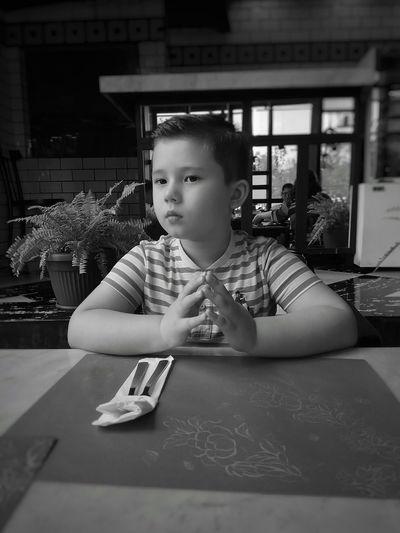 Cute boy sitting at restaurant table