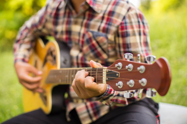 Midsection of man playing guitar while sitting on grass