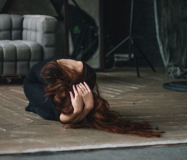 Woman With Hand In Hair Kneeling On Floor At Home