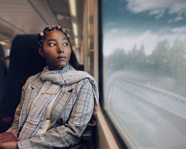 Portrait of teenage boy looking through train window