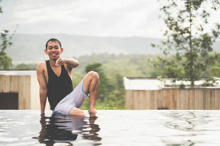 Portrait of a happy young Asia man pointing and looking the camera. Male sitting on infinity edge pool among mountail view and sea of cloud. Copy Space Smiling Happy Fun Relaxing Tourism Travel Vacations Weekend Water Infinity Pool Looking At Camera Leisure Activity Lifestyles Sitting Portrait Nature Pointing Excitement Expedition Feeling Freedom Mountain Resort Nature