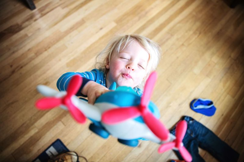 High Angle View Of Boy Playing With Toy Airplane On Hardwood Floor At Home