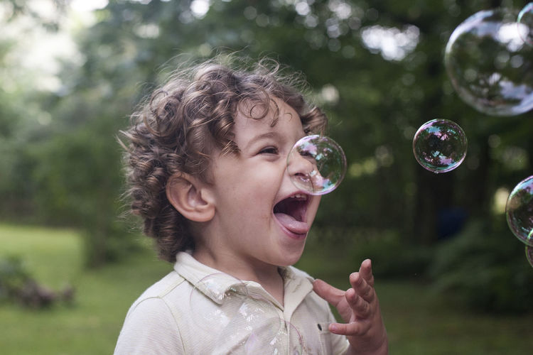 Boyhood Bubbles Fun Blowing Boy Bubble Bubble Wand Child Childhood Day Focus On Foreground Fragility Hairstyle Hapiness Headshot Joy Leisure Activity Lifestyles Nature One Person Outdoors Playing Portrait Real People Vulnerability  Moments Of Happiness Analogue Sound